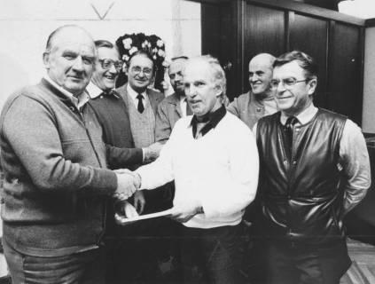 ARH Slg. Bartling 2023, Der Vorsitzende des Versehrtensportvereins Kurt Dahlke (l.) überreicht dem N. N. eine Urkunde, im Hintergrund mehrere Vereinskollegen, um 1975