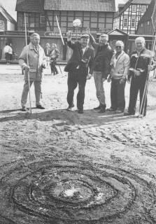 ARH Slg. Bartling 2024, Auf dem Grundstück der Baulücke Windmühlenstraße 25 wirft Bürgermeister Henry Hahn zusammen mit vier anderen Männern einen Speer in ein Zielfeld aus konzentrischen Kreisen, die in den Sand geritzt worden sind, Neustadt a. Rbge., um 1975