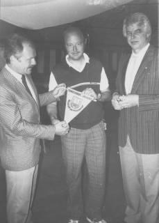 ARH Slg. Bartling 2025, Gruppenporträt mit drei Mitgliedern des Tennis-Vereins Blau-Weiss Neustadt, in der Mitte der Textilkaufmann Gerhard Ohlau, einen Vereins-Wimpel in die Kamera zeigend, Neustadt a. Rbge., um 1975