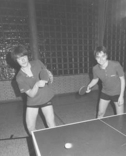 ARH Slg. Bartling 2030, Zwei junge Tischtennisspieler beim Spiel am Tisch in einer Turnhalle, im Hintergrund eine Wand aus Glasbausteinen, um 1975