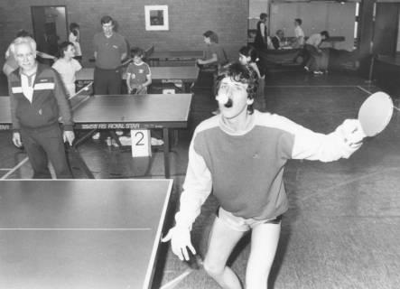 ARH Slg. Bartling 2031, Junge Tischtennisspieler beim Training an mehreren Tischen in einer Turnhalle, im Vordergrund ein Spieler beim Aufschlag, neben den Tischen die Trainer, um 1975
