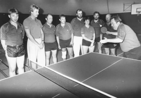ARH Slg. Bartling 2034, Jugendliche und Erwachsene in Sportkleidung am Tischtennistisch in einer Turnhalle stehend und einem Tischtennisspieler beim Aufschlag zuschauend, um 1975