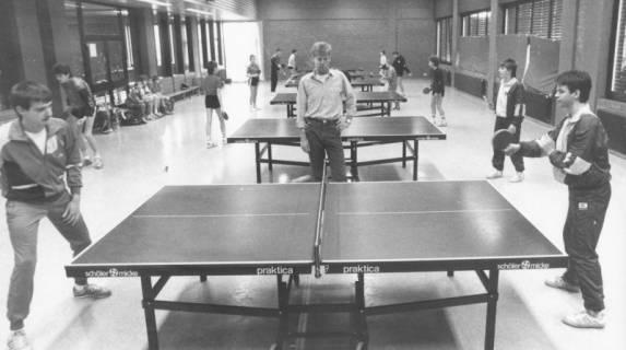ARH Slg. Bartling 2035, Tischtennisspieler und -spielerinnen beim Training an mehreren Tischen in einer Turnhalle, hinter dem ersten Tisch ein Trainer, Blick durch die Mitte, um 1975