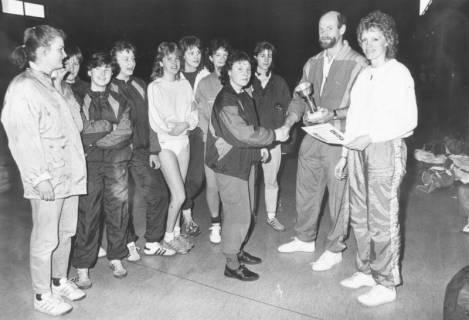 ARH Slg. Bartling 2038, Überreichung eines Pokals und einer Urkunde an junge Hallenhandballerinnen (?) durch einen Mann und eine Frau in einer Turnhalle, um 1975
