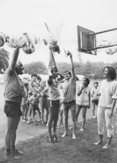 ARH Slg. Bartling 2040, Kinder auf einem Sportplatz versuchen mit einer spitzen Mütze auf dem Kopf nach Ballons, die mit Wasser gefüllt sind und auf einer Leine an einem Basketballkorb aufgereiht sind, zu springen und sie dadurch zum Platzen zu bringen, um 1975