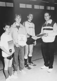 ARH Slg. Bartling 2041, Verleihung von Urkunden an drei junge Sportler in einer Turnhalle durch einen Lehrer der Realschule (?), um 1975