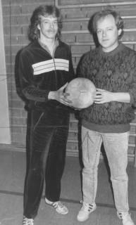 ARH Slg. Bartling 2043, Doppelporträt von zwei jungen Männern, die nebeneinander vor einer verklinkerten Wand in einer Turnhalle stehen und gemeinsam in den Händen einen Fußball präsentieren, um 1975