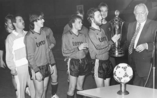 ARH Slg. Bartling 2044, Vergabe eines großen Pokals in einer Sporthalle durch Bürgermeister Henry Hahn (r.) an die Spieler einer Mannschaft im Trikot der Firma Temps, vorn auf dem Tisch ein Fußball, um 1975
