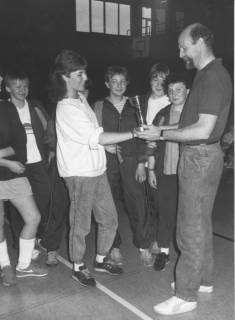 ARH Slg. Bartling 2046, Vergabe eines Pokals in einer Sporthalle durch einen Mann (r.) an die Spielführerin einer Basketball-Schülerinnenmannschaft (?), um 1975