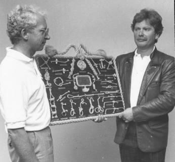 ARH Slg. Bartling 2052, Zwei Männer, nebeneinander stehend und sich anschauend, präsentieren aus Anlass der Einweihung eines Segel-Clubheims (?) eine Knotentafel, um 1975