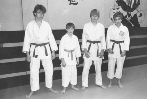ARH Slg. Bartling 2054, Gruppenporträt von vier jugendlichen Karateka im Karate-Gi in einem Übungsraum mit bemalter Wand, um 1975