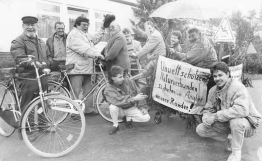 """ARH Slg. Bartling 2055, Gruppe von Anglern vor der Abfahrt mit Fahrrädern zu einer Demonstration; zwei junge Männer kniend und ein Plakat haltend mit der Aufschrift: """"Umwelt schützend, naturverbunden, so drehen wir Angler unsere Runden!"""", um 1975"""
