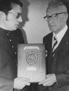 ARH Slg. Bartling 2095, Überreichung des DSB-Wanderpreises an Heinz Göing (r.) durch N. N., den Preis (DSB-Monogramm mit 2 Schrifttafeln auf Holzplatte) präsentierend, 1972