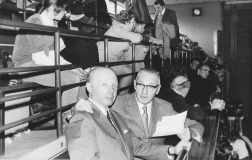 ARH Slg. Bartling 2097, Zwei ältere Männer mit anderen Zuschauern sitzend auf der Tribüne einer Turnhalle, Blick von rechts auf die erste Reihe, um 1975
