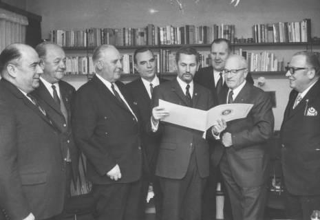 ARH Slg. Bartling 2099, Gruppenbild mit älteren Herren die nebeneinander vor einer Wand mit Bücherregal stehen und in ein Doppelblatt blicken, das von Günther Skirke gehalten wird, 1970